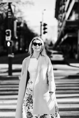 Outdoor fashion portrait of beautiful woman with blond hair, wearing white fashionable dress and coat, crossing road, black and white image