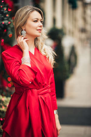 Christmas portrait of beautiful woman with blond hair, wearing red dress and diamond set of earings with bracelet
