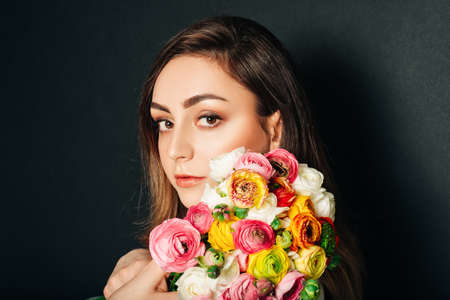 Studio close up portrait of beautiful young woman with long shiny hair, professional makeup, wearing white dress, holding colorful buttercup flowers