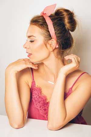 Studio shot of beautiful young woman with blond hair, chignon bun, wearing pink cami top , posing on white background, skin perfection