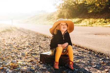 Ritratto all'aperto di una ragazza adorabile e carina che indossa un grande cappello, un cappotto nero e una calzamaglia gialla, seduta su una vecchia valigia vintage Archivio Fotografico