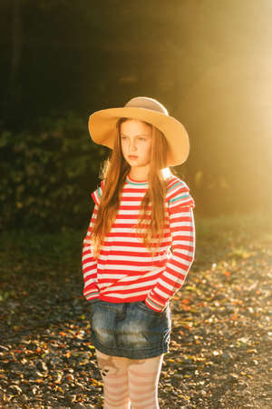 Outdoor portrait of pretty girl wearing big hat, pink stripe pullover and denim skirt