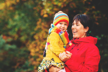 Autumn portrait of happy young mother holding cute little daughter, bright fall fashion