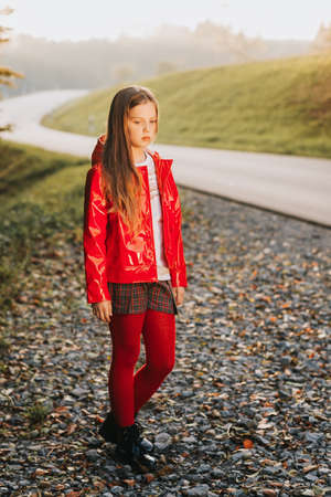 Outdoor portrait of pretty girl wearing red jacket, fashion kid model