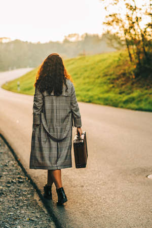 Beautiful woman walking away down the road, wearing long coat, holding old vintage suitcase, back view Фото со стока