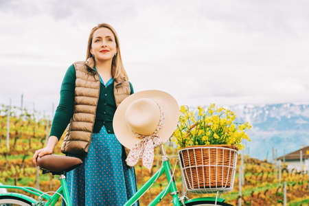 Retro styled portrait of beautiful young woman, wearing vintage clothes, holding mint color bicycle with yellow flowers placed in basket