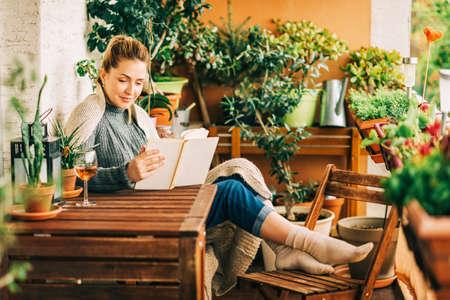 Junge schöne Frau, die sich auf einem gemütlichen Balkon entspannt, ein Buch liest, einen warmen Strickpullover trägt, ein Glas Wein auf einem Holztisch