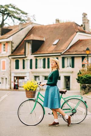 Portrait de style rétro d'une belle jeune femme, portant des vêtements vintage, tenant un vélo de couleur menthe avec des fleurs jaunes placées dans un panier