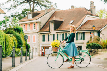 Retro styled portrait of beautiful young woman, wearing vintage clothes, holding mint color bicycle with yellow flowers placed in basket Banque d'images