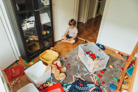 Ritratto in interni di un bambino che gioca in una stanza molto disordinata, lanciando un orsacchiotto sul pavimento