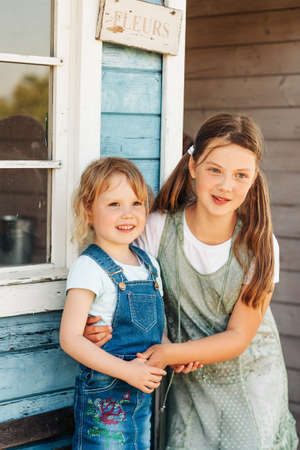 Outdoor portrait of two funny sisters hugging each other and laughing, happy childhood in countryside. French sign on the wall fleures - flowers
