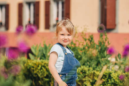 Outdoor portrait of cute little 3-4 year old girl, wearing denim pinafore, playing in garden