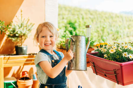 Adorable 3-4 years old kid girl watering yellow daisy flowers on sunny balcony, homework activity for children