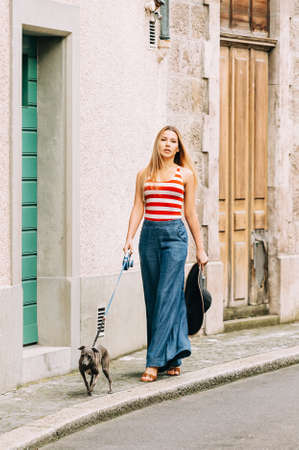 Young blond woman walking her dog on city street, wearing red and white stripe vest and denim wide leg jean
