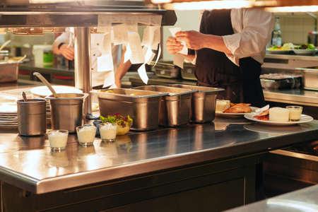 Órdenes de comida en la mesa de la cocina del restaurante, órdenes de lectura del jefe y cocina en la cocina profesional del restaurante. Foto de archivo