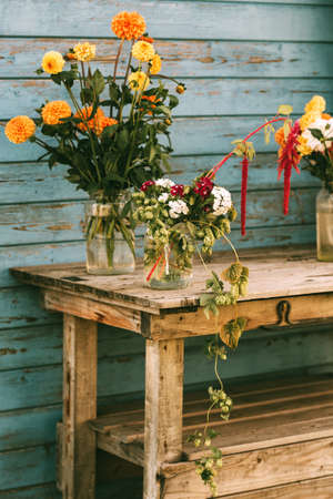 Fall flowers in glass jars standing on the table outside