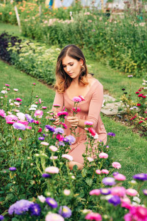Pretty young woman working in autumn garden, girl taking care of colorful chrysanthemum, gardener enjoying warm and sunny day