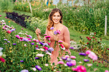 Pretty young woman working in autumn garden, girl taking care of colorful chrysanthemum, gardener enjoying warm and sunny day Reklamní fotografie - 130070579