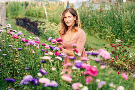 Pretty young woman working in autumn garden, girl taking care of colorful chrysanthemum, gardener enjoying warm and sunny day Reklamní fotografie - 130070584