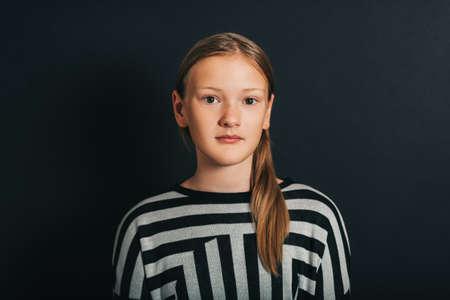 Dark studio portrait of young kid girl wearing stripe pullover