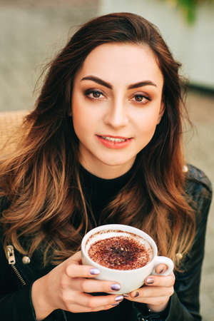 Beautiful young woman drinking coffee on a terrace