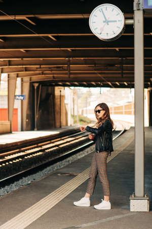 Young woman waiting for the train on a train station