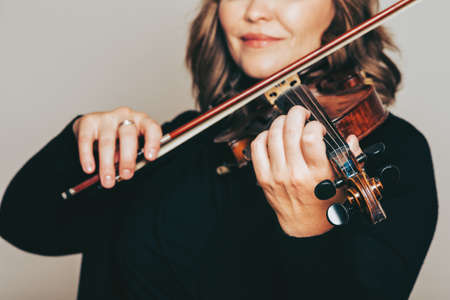 Studio close up portrait of beautiful woman with violin, white background