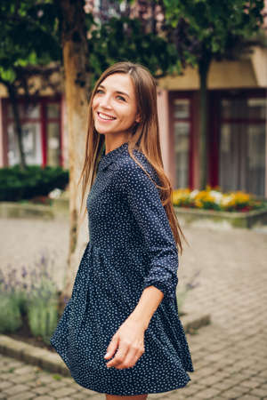 Outdoor portrait of happy laughing woman, wearing mini dress