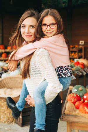 Happy young mother holding daughter on her back, Sunday market day in autumn