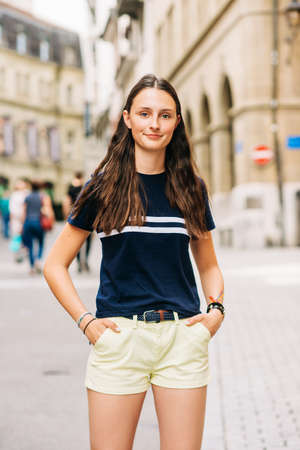 Outdoor portrait of pretty teenage girl on the city street