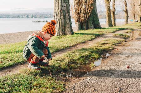 Netter Kleinkindjunge, der draußen mit Schlammpfütze spielt, warme Jacke und Winterstiefel trägt, glückliche Kindheit