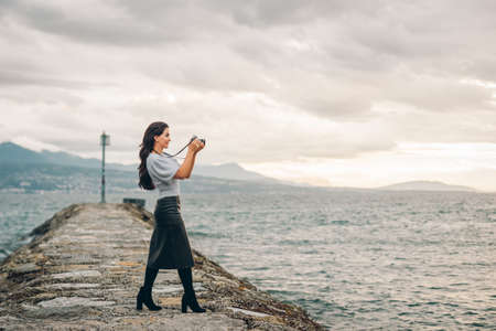 Young beautiful woman taking pictures outside with vintage film camera, wearing black leather skirt Imagens - 134661239