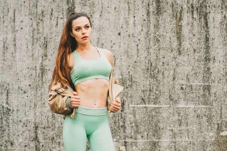 Openluchtportret van jonge, mooie fitte vrouw, gekleed in groene activewear, atleetmodel poseren naast grijze stedelijke muurachtergrond, sportmode