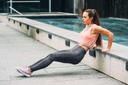 Outdoor portrait of young beautiful fit woman doing tricep dips, wearing fashionable activewear, athlete model posing in urban background, sport fashion