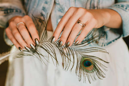 Stylish trendy female mirror manicure, metal nail art, holding peacock feather