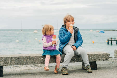 Two funny kids eating ice cream by the lake on a rainy day Stock Photo