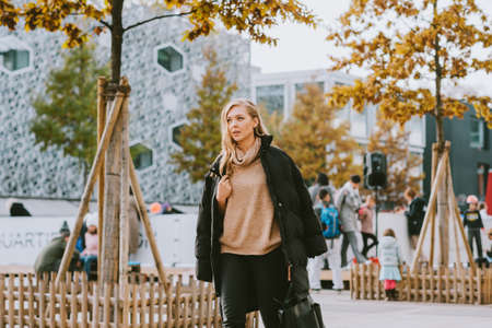 Street fashion portrait of young beautiful woman wearing beige roll neck pullover and black padded coat