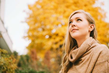 Herfstportret van jonge mooie vrouw die een beige coltrui draagt, omhoog kijkend