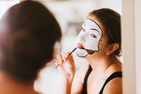 Woman actress looking in the mirror and doing mime makeup