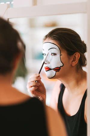 Attrice donna che si guarda allo specchio e si trucca da mimo