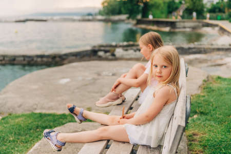 Little girls playing by the lake in summertime, children having fun outside, resting on the bench Standard-Bild