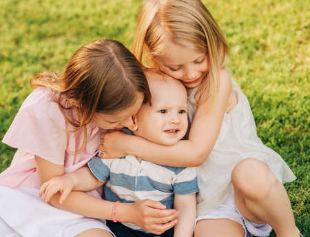 Girls playing adorable baby brother in summer park Stock Photo - 136745976