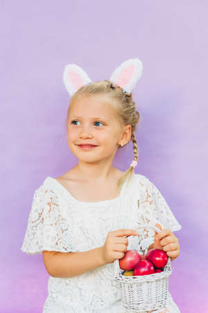 Cute little girl wearing bunny ears, holding white basket full of painted eggs, posing on pink background, Easter concept