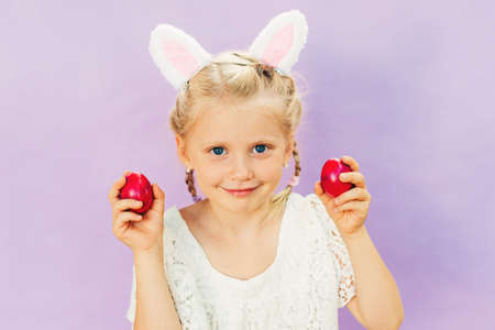 Cute little girl wearing bunny ears, holding purple painted eggs, posing on pink background, Easter concept Stockfoto