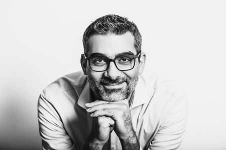 Black and white portrait of handsome man wearing blue shirt and glasses, leaning on hands, posing on white background