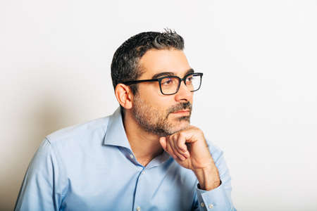 Studio portrait of handsome man wearing formal blue shirt and glasses, posing on white background, leaning on one hand, looking on the side