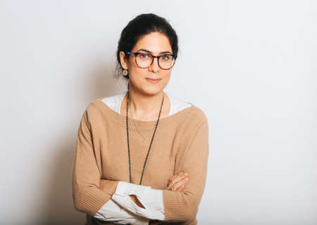Studio portrait of beautiful brunette woman, wearing glasses, arms crossed, posing on white background