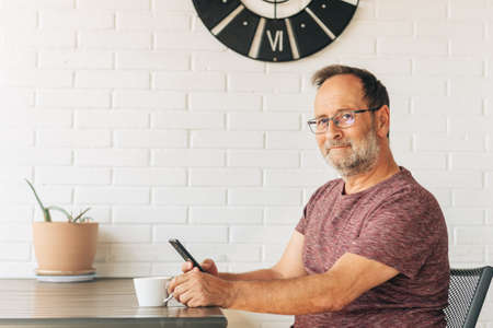 Middle age man relaxing on balcony, drinking cofee, using smart phone