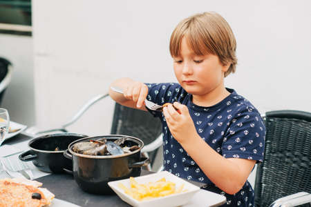 Child eating steamed mussels with french fries in outdoor restaurant Foto de archivo