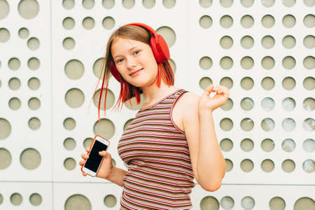 Outdoor portrait of happy young teen girl with stylish red dyed short hair, child listening music with headphones, holding phone